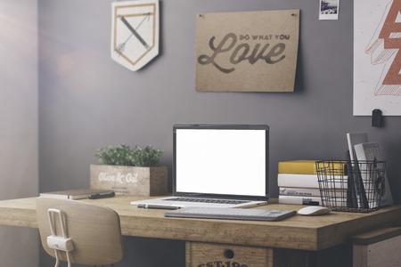 Stijlvolle werkruimte met computer en posters aan huis of atelier Stockfoto