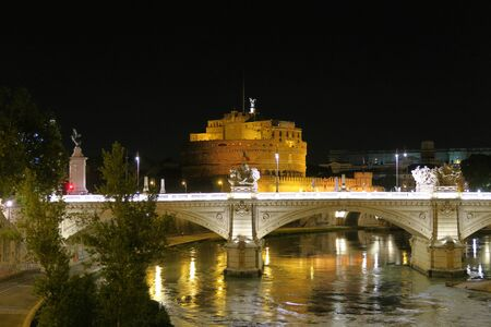 Rome a bridge on Tiber river before Castel SantAngelo at night. Ponte SantAngelo castle visible in the background at Rome Italy. Editorial