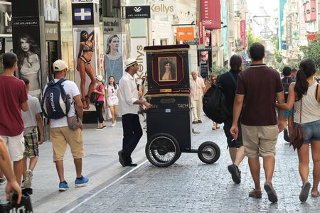 decades: Athens, Greece - August 06 2016: A laterna (piano barrel) player at Ermou street. Laterna players used to walk the streets in past decades in return for money for the music they played. Editorial