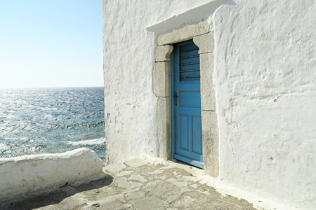 Mykonos, Greece – A blue door on a whitewashed wall. The entrance to one of the five churches that form The Church of Panagia Paraportiani. Stock Photo