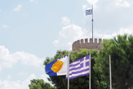 Thessaloniki, Greece municipal and Greek flag. The flag is waving before the White Tower, the landmark of the city and depicts Alexander the Great at ancient coin. Editorial