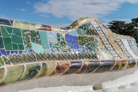 seating area: Barcelona, Spain Park Guell mosaic seating at Nature Square Placa de la Natura. Mosaic seating area with multi-coloured tiles at at Nature Square Placa de la Natura.