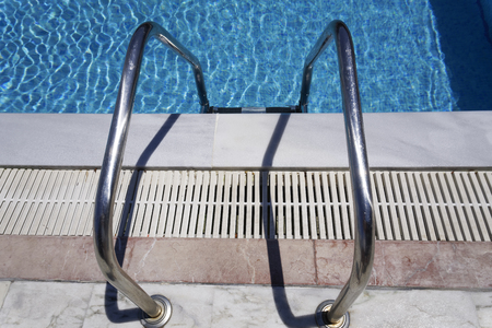 openair: Outdoor swimming pool ladder. Grab bars metal ladder to a blue water open air pool on a sunny day.