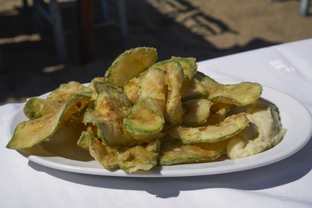 Fried zucchini chips with garlic mash served on a white dish by the beach. Fried zucchini with scordalia recipe, greek potato and garlic dip, on on white linen tablecloth.