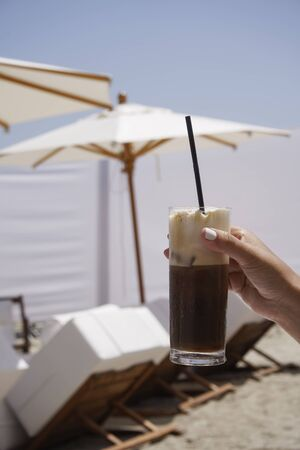 non alcoholic: Iced coffee in hand with blurred beach background. Female hand holding an iced glass of cappuccino freddo coffee with a black straw, on a sunny summer day.
