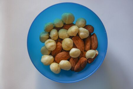 Macadamia and almonds mixed roasted nuts top closeup view. Collection of healthy nuts served on a blue plastic bowl. Stock Photo