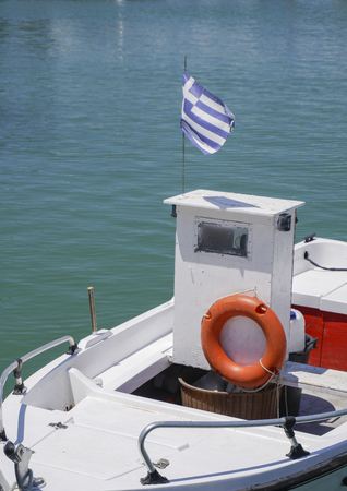 Small fishing boat with orange lifebuoy and Greek flag waving. White boat with swim ring floating by the seafront at Greece on a sunny summer day.