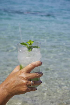 alcoholismo: Cocktail drink in hand with blurred beach background. Female hand holding an iced glass of mojito alcoholic cocktail with mint and sliced lime, on a sunny day.