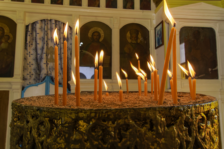 Lit candles on a church candelabrum. Thin candles with flame on a manuale with sand and blurred image of saints icons at an Orthodox church.