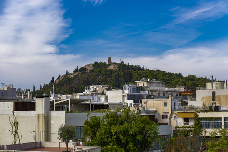 Athens, Greece Philopappos Monument day view and cityscape. Panoramic view from the Acropolis of Athens of Tomb and monument ruins on the Greek capital. Stock Photo