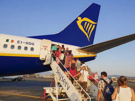 Passengers board on tarmac of Thessaloniki airport, Greece. Evening view of travelers at apron area of Thessaloniki International airport Makedonia, boarding from rear entrance of a Ryanair aircraft.