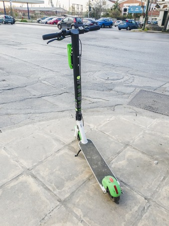 Parked Lime electric Scooter rental without passenger. A green and black ride sharing Lime-S electric scooter ready to be used by the next rider on the streets of Thessaloniki, Greece.