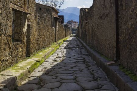 Pompeii, Italy secondary narrow street along remaining houses. Day view of structured formation of cobblestoned path to accommodate traffic inside the town. Banque d'images