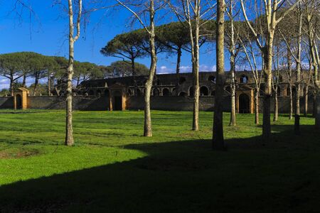 Pompeii, Italy Palestra Grande courtyard. Large central space for gymnastic exercises, Palestra of Gymnasium, with background view of stone built 20.000 capacity Roman Anfiteatro di Pompeii.