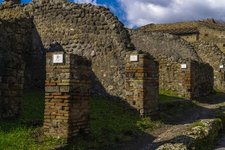 Pompeii, Italy Roman architecture city block remains with numbered homes entrances. Numbers in doorways identifying stone houses ruins, insula, after Mount Vesuvius volcanic eruption in 79 AD. 스톡 콘텐츠 - 133240541