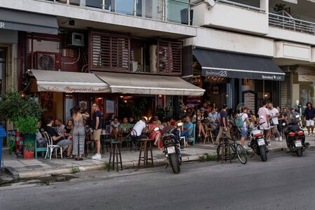 Thessaloniki, Greece people enjoy coffee at city center cafe bars. Unidentified crowd drinking frape or other beverage at outdoors seating bars in Nikis Avenue before the waterfront.