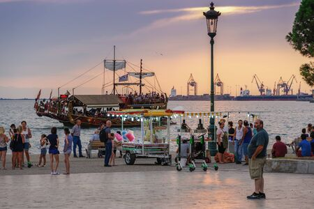 Thessaloniki, Greece golden hour at waterfront with crowd. Thermaikos gulf seafront evening with street vendors & trailer selling cotton candy or popcorn before White Tower landmark. Sajtókép