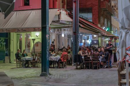 Thessaloniki, Greece Hellenic nightlife scene of people at outdoors tavern restaurants. Unidentified crowd eating & drinking at tavernas in the center at Athonos area.