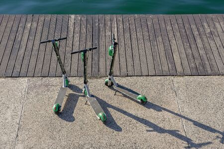 Thessaloniki, Greece Parked Lime Electric Scooter rentals without passenger. Three green & black ride sharing Lime-S electric scooters before a wooden waterfront, ready to be used. Editorial