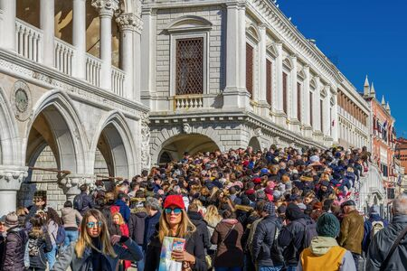 Venice, Italy dense crowd packed on a bridge. Large number of unidentified people walking on Ponte della Paglia before Palazzo Ducale.