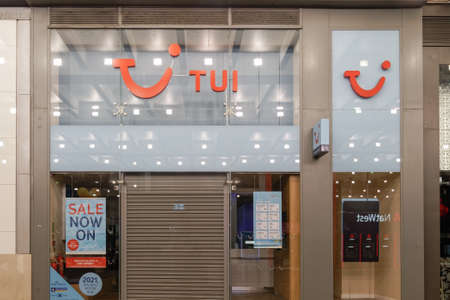 Manchester, UK TUI leisure travel agency closed store entrance with company logo. Night view of window store facade of tour company with travel offers & posters.