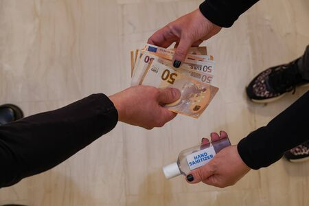 Hand sanitizer buying shortage concept selling antiseptic gel. Woman hands over a waterless alcohol-based bottle for handrubs in exchange for money, to illustrate issue of out of stock disinfectant. Imagens