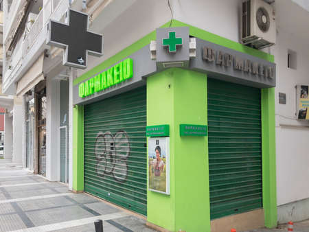 Thessaloniki, Greece closed pharmacy store entrance with sign. External day view of Hellenic shop with illuminated green cross and security shutter gate.