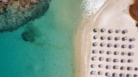 Mediterranean terrain Greek landscape sandy beach drone shot. Aerial day top view of Sithonia Chalkidiki peninsula with crystal clear waters & sea beds with umbrellas next to small rocky island.