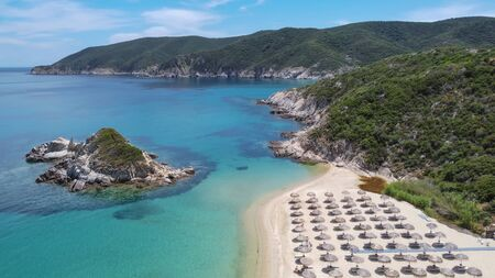 Mediterranean terrain Greek landscape sandy beach drone shot. Aerial view of Sithonia Chalkidiki peninsula with green plantation by crystal clear waters, sea beds with umbrellas & small rocky island. Stock Photo