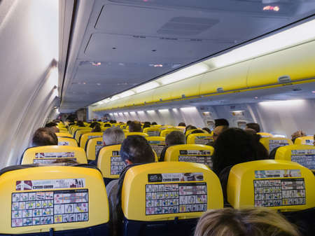 Budapest, Hungary December 10 2019: Passengers inside a Ryanair aircraft cabin, during flight. Interior of a Boeing 737 800 commercial jet full of travellers on typical yellow & blue seats layout. Editorial