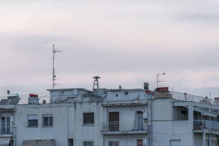 War air raid siren on residential buildings rooftop. Evening view of old mushroom shaped attack warning siren, between antennas and satellite dishes on top of city houses in Thessaloniki, Greece. Banque d'images