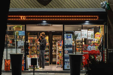 Thessaloniki, Greece - November 20 2020: Customer at shop entrance with covid-19 mask. Convenience store with clerk serving male wearing face protection to prevent coronavirus spread.