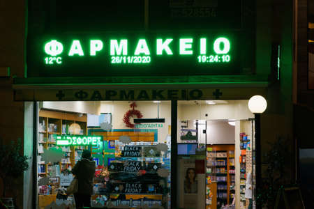 Thessaloniki, Greece November 26 - 2020: Greek open pharmacy store entrance. External night view of Hellenic pharmaceutical shop with illuminated green sign and window showcase.