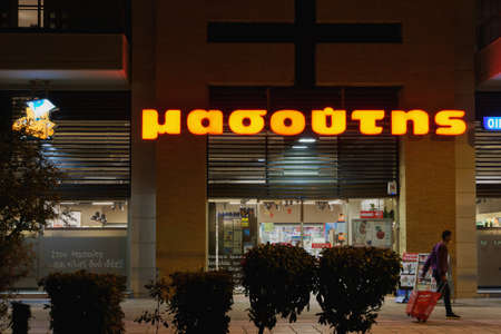 Thessaloniki, Greece - November 26 2020: Masoutis supermarket chain entrance with logo. Hellenic hypermarket store facade illuminated view, with person with face mask holding shopping basket outside. Editöryel