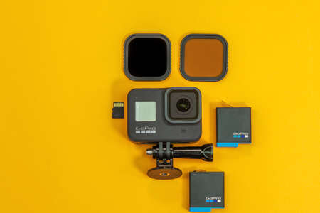 Thessaloniki, Greece - November 8 2020: GoPro 8 black with logo and accessories top view. Flat lay of action camera with memory card & battery at yellow background with lens filters on table.