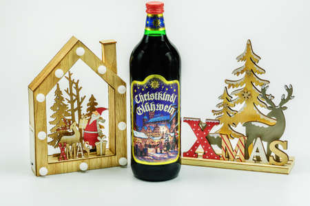 Thessaloniki, Greece - November 8 2020: Aromatic mullet Christmas wine bottle with decorations. Spiced alcoholic beverage drink bottle with Advent Feast festive seasonal figures on white background.