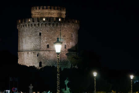 Thessaloniki Greece night view of The White Tower with Christmas lights decoration around. The city's landmark with illuminated seasonal instalments under dark sky.