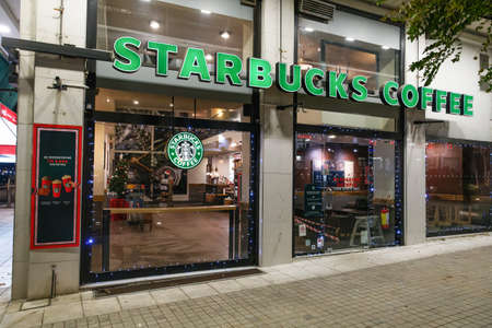 Thessaloniki, Greece - November 6 2020: Starbucks Coffee Store with Medusa logo and seasonal decoration. External evening view of famous coffeehouse chain store with Christmas beverages illustration.