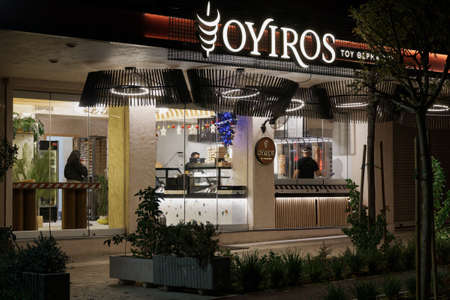 Thessaloniki, Greece - December 6 2020: Hellenic empty gyros shop without crowd. Illuminated night view of grill restaurant only accepting orders for take away & deliveries, due to covid-19 measures. Editöryel