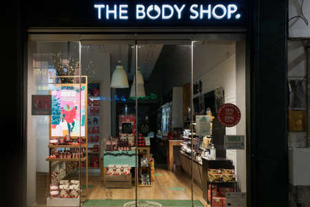 Thessaloniki, Greece - December 6 2020: The Body Shop facade with logo. Illuminated night view of British cosmetic, skin care and perfume closed store entrance with sign and products on window display