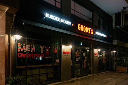 Thessaloniki, Greece - December 6 2020: Goodys burger house without crowd. Illuminated night view of closed grill restaurant only accepting orders for take away & deliveries, due to covid-19 measures.