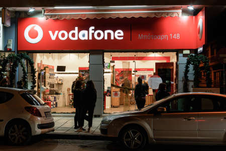 Thessaloniki, Greece - December 8 2020: Vodafone telecommunications store facade with logo. Illuminated night view of crowd at store entrance of Hellenic mobile operator.