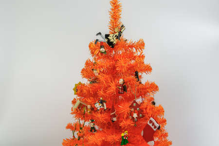 Artificial orange Christmas tree with ornaments against white background. Wooden miniature festive decorations hanging on colourful branches of seasonal miniature. Stok Fotoğraf