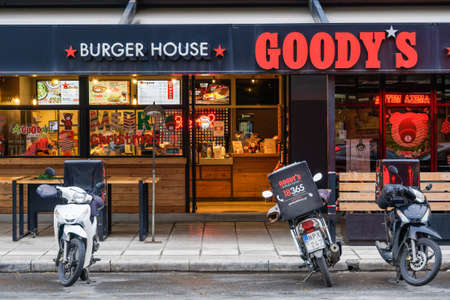 Thessaloniki, Greece - December10 2020: Goodys burger house with delivery motorbikes outside. Evening view of grill restaurant only accepting orders for take away & deliveries due to covid-19 measures