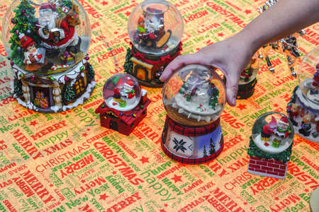 Hand decorating many Christmas snow globe balls on a table. Female putting festive Xmas dome balls depicting Santa Claus and other seasonal figures on a surface.
