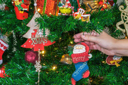 Female hand hanging seasonal ornaments on a tree with lights. Festive colourful decorations before an illuminated artificial tree with Merry Christmas message hanging from a brunch.