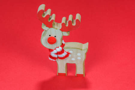 Advent Feast festive Christmas wooden decoration with reindeer. Seasonal colorful miniature figure before red background. Stok Fotoğraf