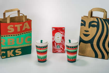 Thessaloniki, Greece - December 14 2020: Starbucks Christmas Blend takeaway cups. Branded seasonal beverage mugs and filter coffee with company logo bags against white background.