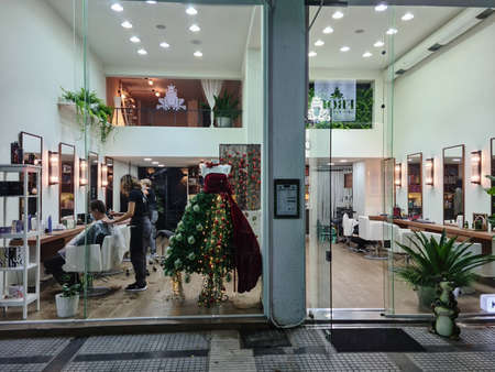 Thessaloniki, Greece - December 17 2020: Hairdresser cutting hair of male wearing covid-19 mask. Illuminated night view of customer with face protection at salon with modern decorated Christmas tree. Editöryel