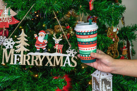 Thessaloniki, Greece - December 14 2020: Starbucks Christmas Blend takeaway coffee cup. Hand revealing branded seasonal beverage mug with company logo before a decorated lit tree. Editöryel